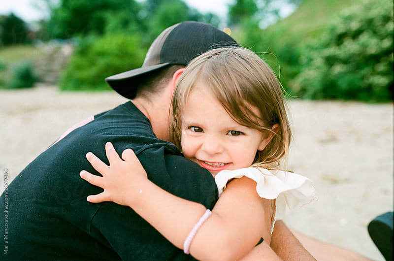 girl gives dad a hug by Maria Manco for Stocksy United
