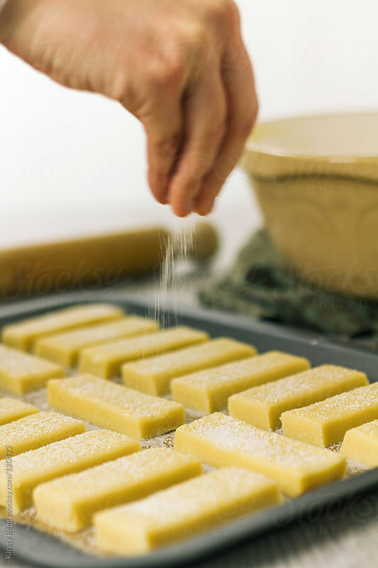 Sprinkling sugar onto unbaked shortbread by Kirsty Begg for Stocksy United
