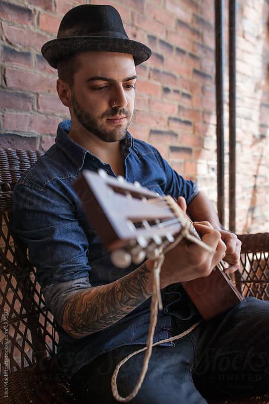 handsome brazillian man wearing fedora, playing guitar by Lisa MacIntosh for Stocksy United
