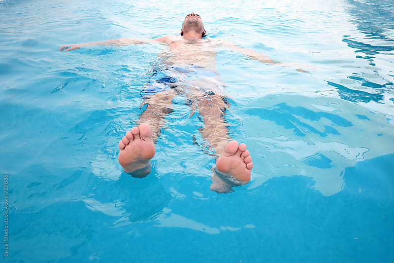 Man floating on the water of a swimming pool by Bisual Studio for Stocksy United
