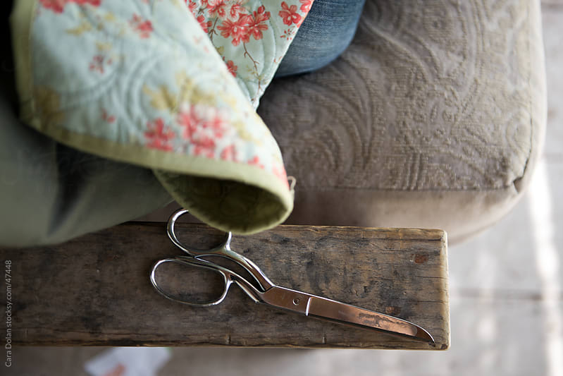 Scissors lay next to a quilt in progress by Cara Dolan for Stocksy United