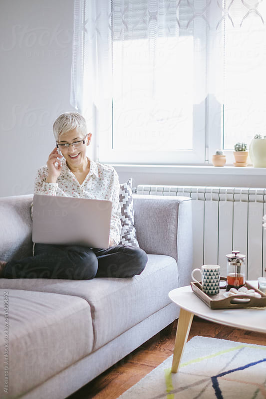 Senior Woman Sitting in the Living Room with Laptop and Using Phone by Aleksandra Jankovic for Stocksy United