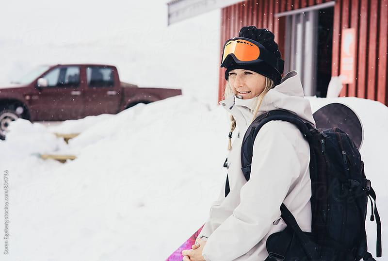 Female snowboarder sitting in the snow holding snowboard by Soren Egeberg for Stocksy United