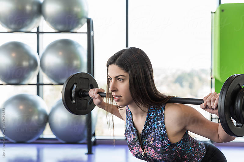 Closeup of female athlete exercising with barbell in a studio by Lior + Lone for Stocksy United