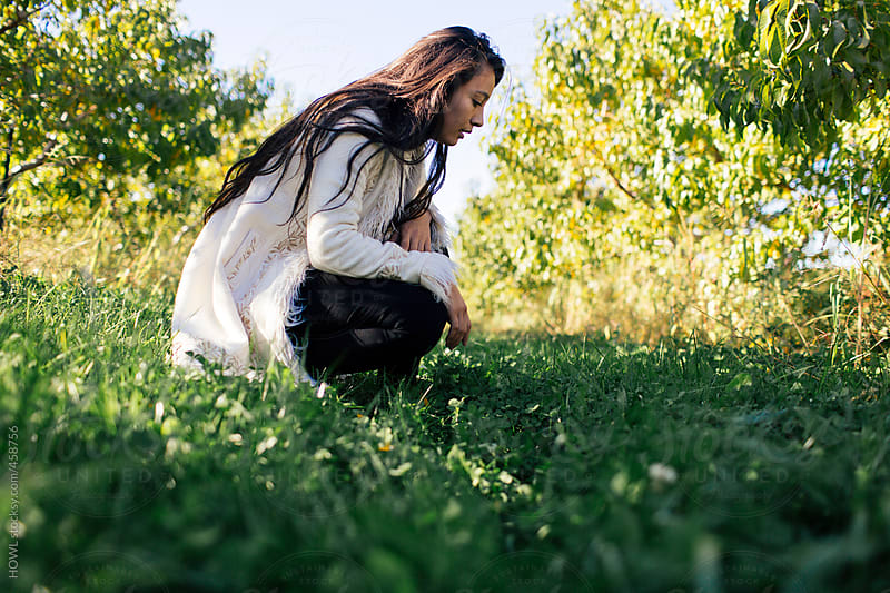 beautiful girl crouches in an apple orchard examines the ground by HOWL for Stocksy United