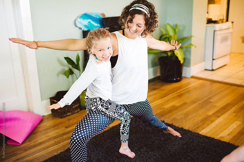 Mother and daughter doing yoga together at home. by Kate Daigneault for Stocksy United