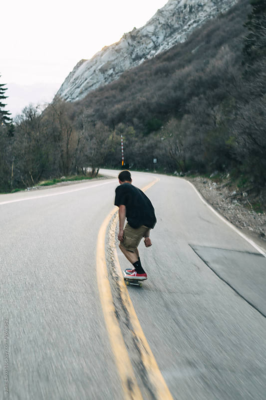 A Skateboarder Bombing Down Hill by Jake Elko for Stocksy United