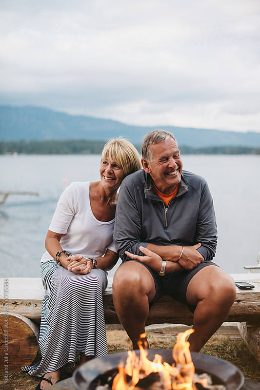 Happy mature couple sitting near fire with lake in background by Rob and Julia Campbell for Stocksy United