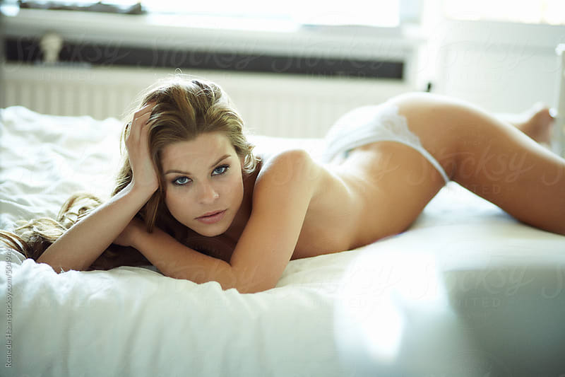 young woman lying on bed, topless by Rene de Haan for Stocksy United