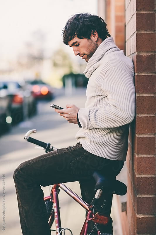 Stylish young man on a bicycle using his phone texting messages by Suprijono Suharjoto for Stocksy United