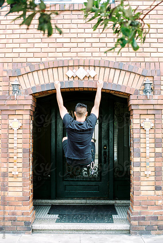 Young man hanging off building entryway by Daniel Kim Photography for Stocksy United