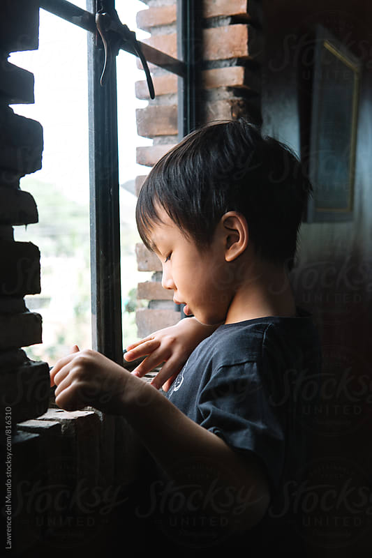 Young cute little boy standing by the window in a restaurant by Lawrence del Mundo for Stocksy United