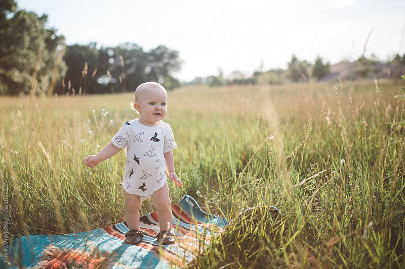 Baby Happily Looking Away in Field by Kim Swain for Stocksy United