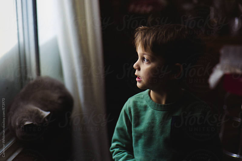 The kid and the cat on a housebound snowday by Cameron Whitman for Stocksy United