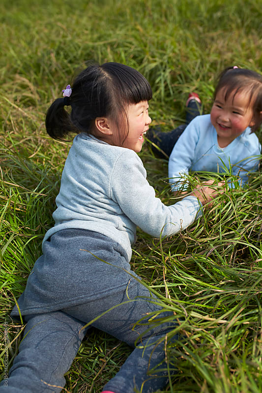 two happy little asian girl in grassland by Bo Bo for Stocksy United