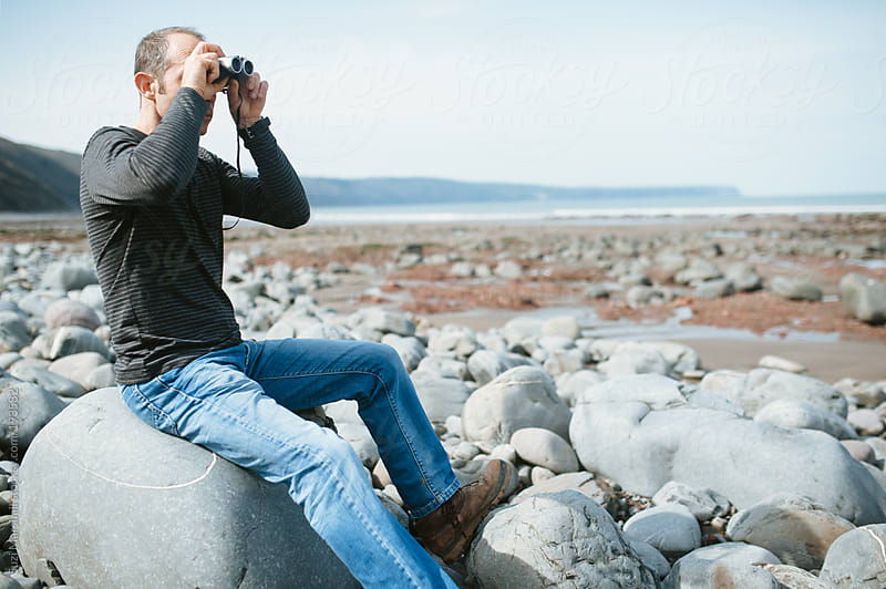 Man sitting on a rock at the beach using binoculars by Suzi Marshall for Stocksy United