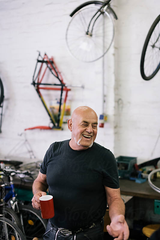 Smiling senior Bicycle Mechanic  by VegterFoto for Stocksy United