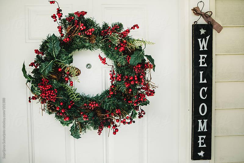 Christmas wreath hanging on the door by Suprijono Suharjoto for Stocksy United