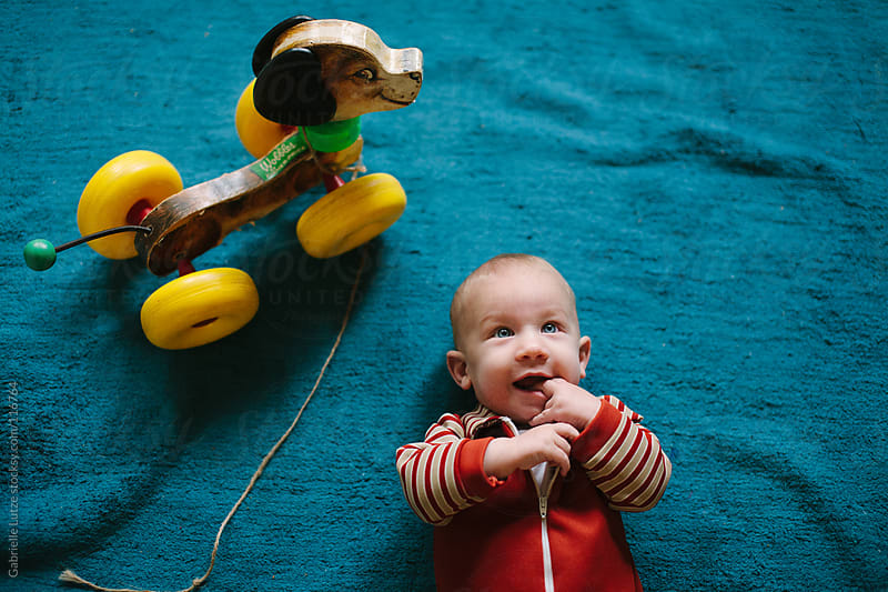 Baby Boy on Floor with Toy Dog by Gabrielle Lutze for Stocksy United