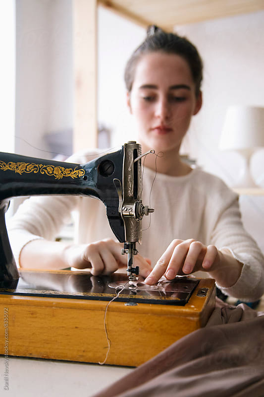Young woman working with vintage sewing machine by Danil Nevsky for Stocksy United