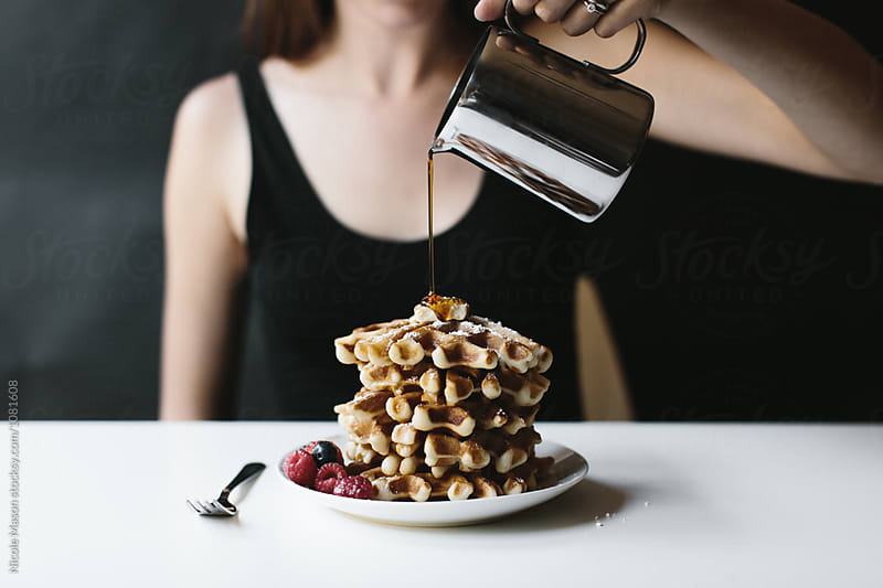 person pouring syrup on stack of waffles on white table by Nicole Mason for Stocksy United