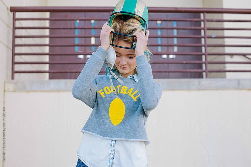 Pretty Girl Taking Football Helmet Off by Gabrielle Lutze for Stocksy United