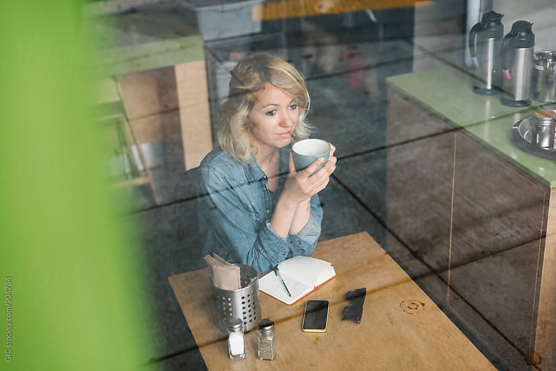 Young blonde woman sitting in a cafe by Simone Becchetti for Stocksy United