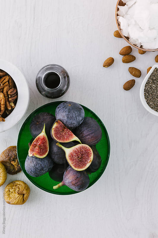 Fresh figs with coconut oil, chia seeds, pecans and maple syrup by Kirsty Begg for Stocksy United