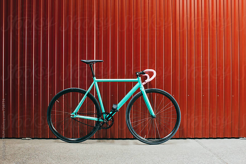 Minimalist Turquoise Fixed Gear Bicycle Leaning Against Shiny Red Metallic Wall by Julien L. Balmer for Stocksy United