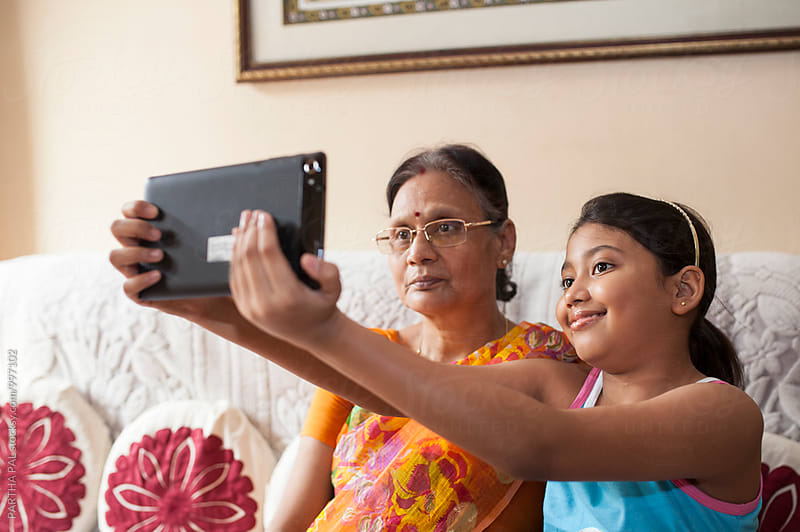 Grand Child taking photo with Grand Mother in a tablet by PARTHA PAL for Stocksy United