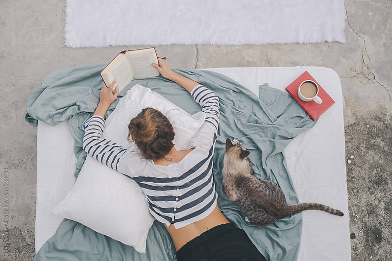 Woman reading book while her cat is sitting next to her by Jovo Jovanovic for Stocksy United