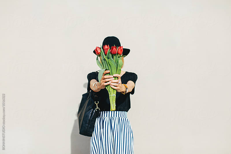 Portrait of a stylish senior woman hiding her face with a bouquet of red tulips.  by BONNINSTUDIO for Stocksy United