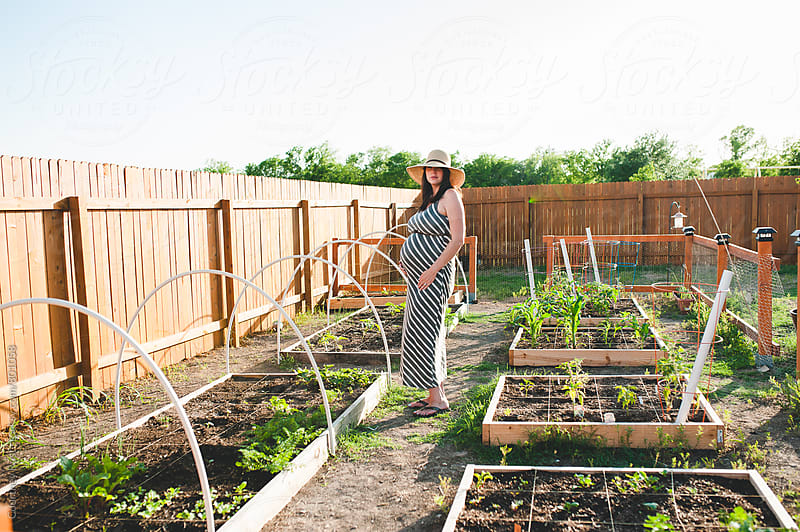 a pregnant gardener by Courtney Rust for Stocksy United