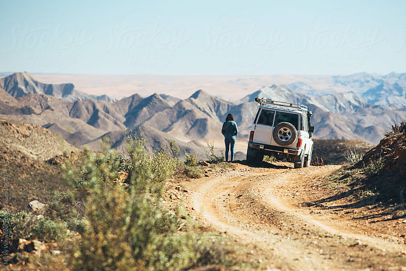 woman standing outside her car whilst on a roadtrip exploring a mountainous desert by Micky Wiswedel for Stocksy United