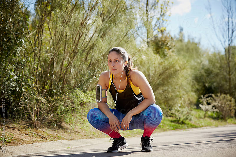 Female Jogger Crouching On Street by ALTO IMAGES for Stocksy United