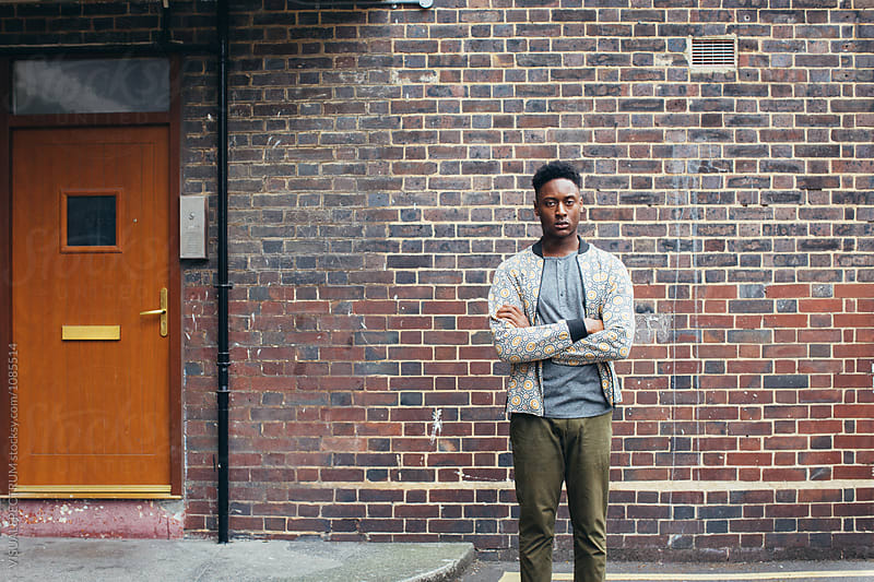 London Street Style - Outdoor Portrait of Young Casual Black Man Standing in Front of Working Class Home by Julien L. Balmer for Stocksy United
