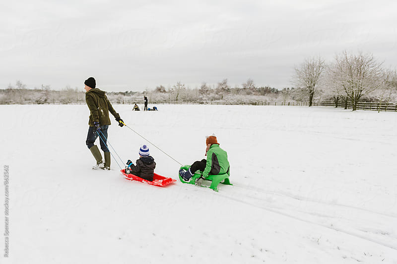 Father pulls his children in 2 sledges across snowy field by Rebecca Spencer for Stocksy United