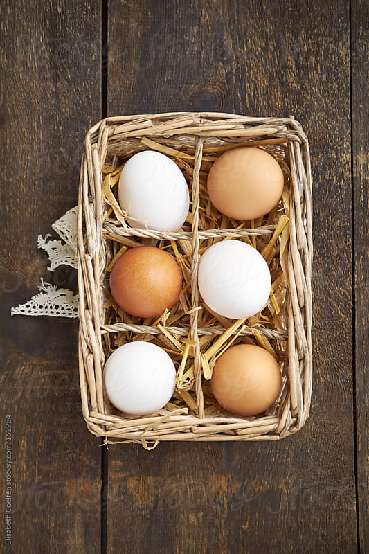 White and brown chicken eggs in a basket by Elisabeth Coelfen for Stocksy United