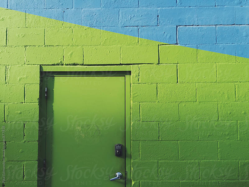 Green doorway and building by Paul Edmondson for Stocksy United