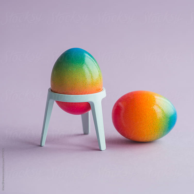 Two rainbow colored eggs on a light purple background by Irina Efremova for Stocksy United