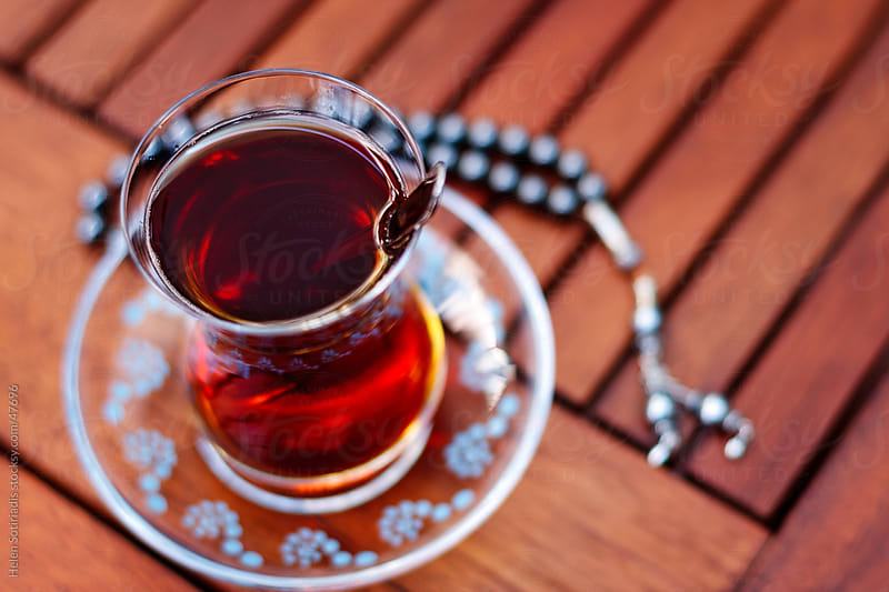 turkish tea on a table with worry beads by Helen Sotiriadis for Stocksy United
