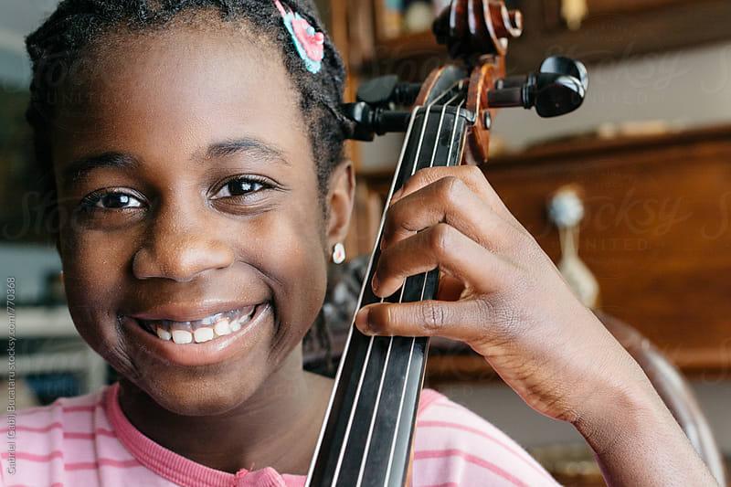 Smiling black girl with cello by Gabriel (Gabi) Bucataru for Stocksy United