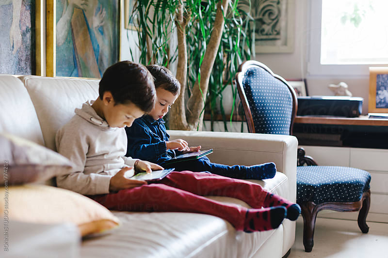 Side view of a little brothers using their digital tablet sitting on the sofa. by BONNINSTUDIO for Stocksy United