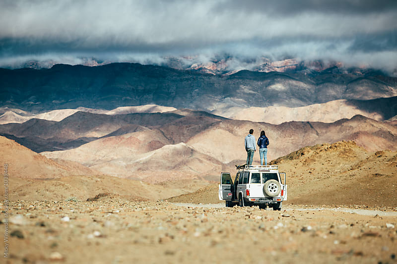 Coupld standing on the roof of their overland truck in a rugged mountain landscape by Micky Wiswedel for Stocksy United