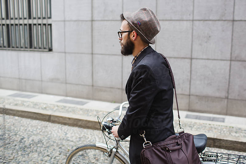 Man with hat and briefcase walking down the street with his city bike by michela ravasio for Stocksy United