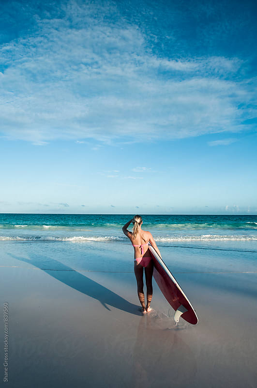 Woman on Beach Carrying a Stand Up Paddleboard by Shane Gross for Stocksy United