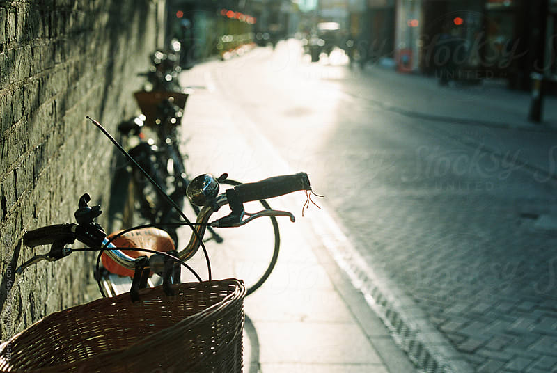 Bicycles parked against a wall on a sunny street.  by Helen Rushbrook for Stocksy United