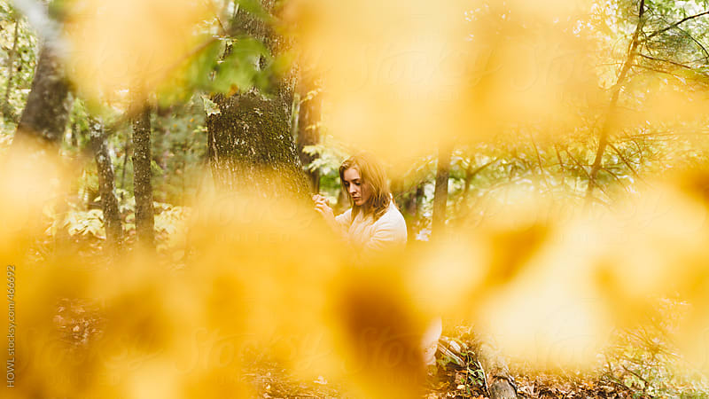 Blonde girl relaxes in  the woods alone  by HOWL for Stocksy United