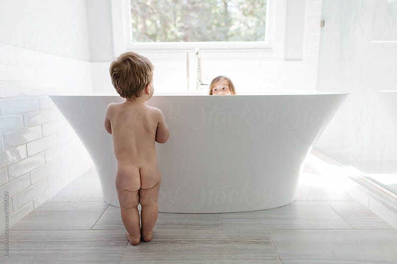 Naked toddler looking at her sister in a big bathtub by Jakob for Stocksy United