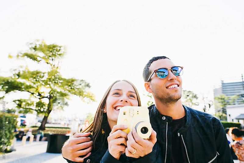 Smiling tourist couple taking a photo with their instant camera.  by BONNINSTUDIO for Stocksy United
